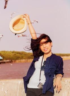 Mulher bonita preto longo cabelo. sorrindo e carregando uma câmera com chapéu até obter o vento de verão