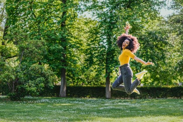 Mulher bonita pulando alegremente em um jardim. vista lateral. corpo todo.