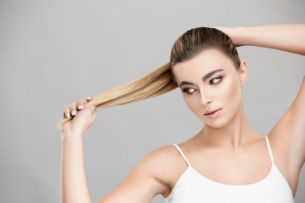 Mulher bonita puxando o cabelo loiro para o lado e olhando para ele isolada no cinza, garota com cabelo comprido natural e maquiagem leve posando