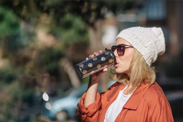 Mulher bonita que aprecia a bebida na rua
