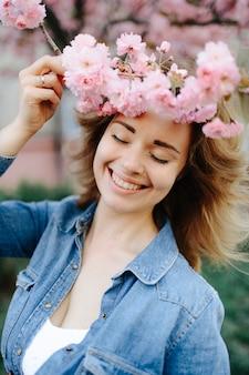 Mulher bonita que aprecia o campo da margarida, fêmea agradável que encontra-se no prado das flores, menina bonita que relaxa ao ar livre, se divertindo, segurando a planta, jovem feliz e natureza verde primavera, conceito de harmonia