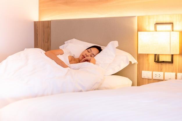 Mulher bonita que dorme bem na cama com o descanso branco macio.