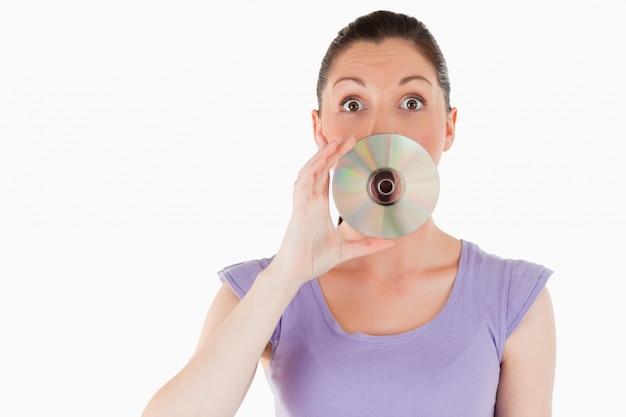 Mulher bonita que esconde a boca com um cd
