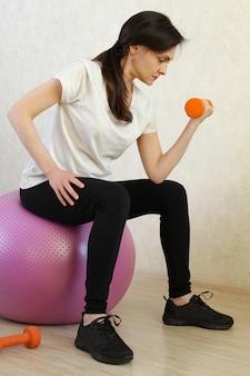 Mulher bonita que exercita com halteres em casa. treino de fitness em casa. pare o coronavírus covid-19. tempo de quarentena