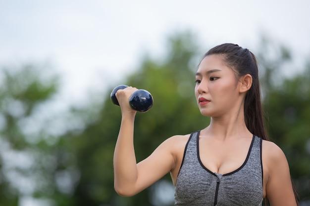 Mulher bonita que exercita o braço levantando halteres no parque.