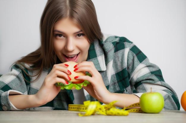 Mulher bonita que faz uma escolha entre alimentos úteis e prejudiciais
