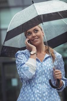 Mulher bonita que guarda o guarda-chuva ao falar no telefone móvel