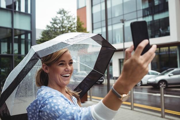 Mulher bonita que guarda o guarda-chuva ao tomar o selfie