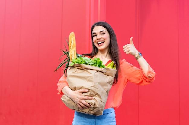 Mulher bonita que guarda sacos de compras na mercearia no fundo vermelho que mostra os polegares.