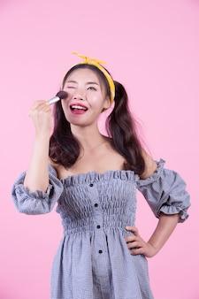 Mulher bonita que guarda uma escova, escovada em um fundo cor-de-rosa.
