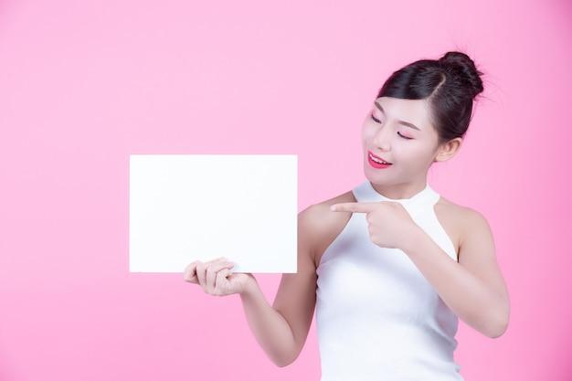 Mulher bonita que guarda uma folha da placa branca em um fundo cor-de-rosa.
