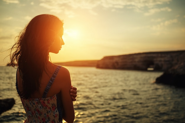 Mulher bonita que olha na distância no por do sol contra o céu.