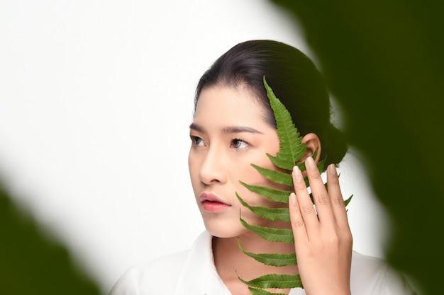 Mulher bonita que prende a planta verde.