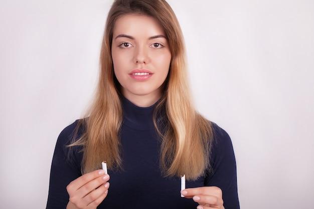 Mulher bonita que prende o cigarro quebrado. parando de fumar
