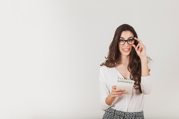Mulher bonita que prende uma agenda e tocando seus óculos