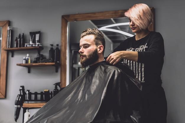 Mulher bonita que prepara o cliente na barbearia