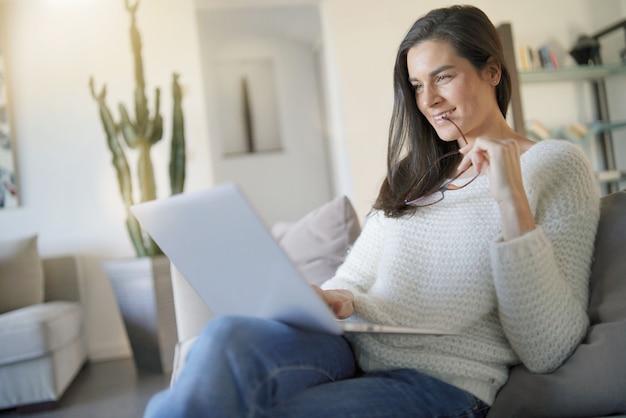 Mulher bonita que relaxa em casa com laptop