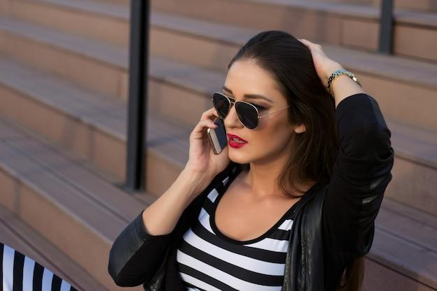 Mulher bonita que senta-se nas escadas e que fala no telefone móvel.