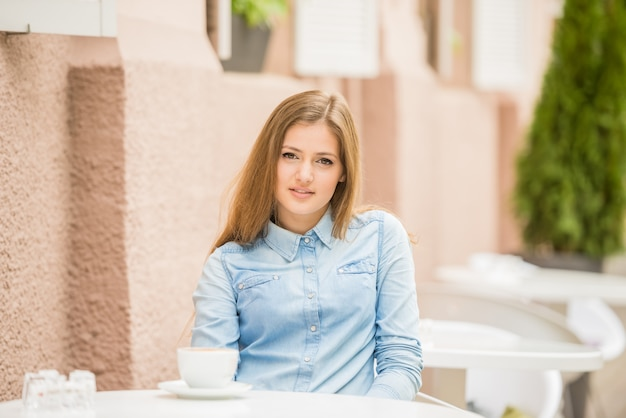 Mulher bonita que senta-se no café do verão com xícara de café
