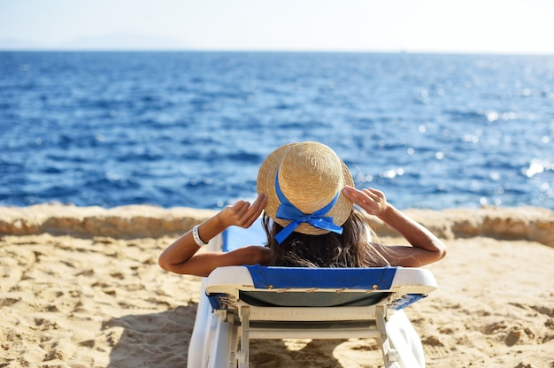 Mulher bonita que sunbathing em uma praia no recurso tropical do curso, apreciando férias de verão.