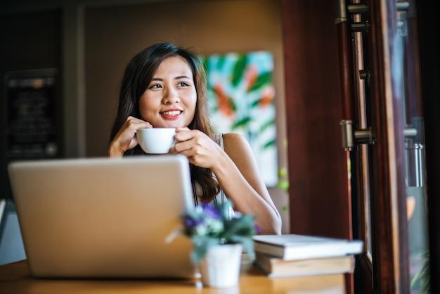 Mulher bonita que trabalha com o computador portátil no café café
