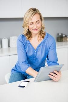 Mulher bonita que usa a tabuleta digital