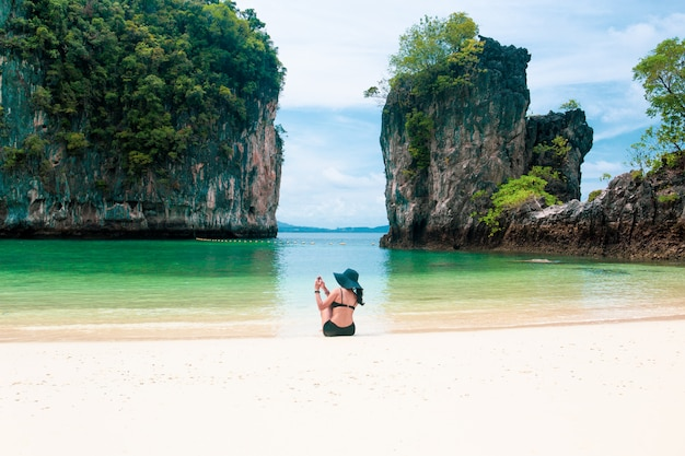 Mulher bonita que veste um chapéu usando o telefone celular que toma uma foto na praia nas férias de verão.