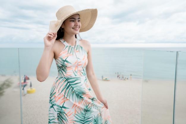 Mulher bonita que veste um vestido bonito que anda nas férias de verão de vidro das escadas.