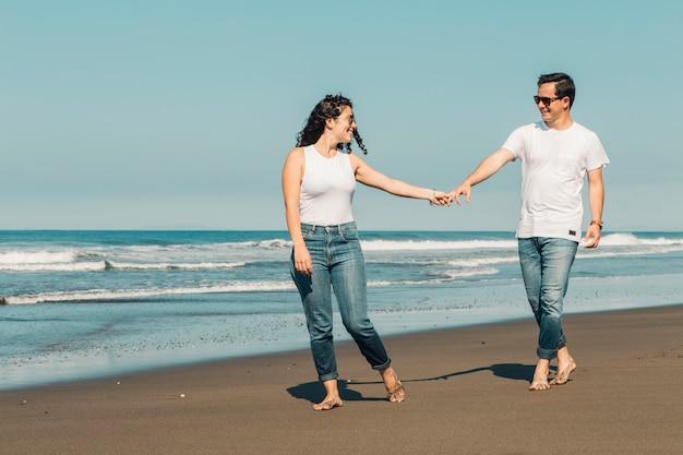Mulher bonita querendo o homem seguir na praia arenosa