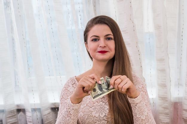 Mulher bonita rasgando nota de cem dólares