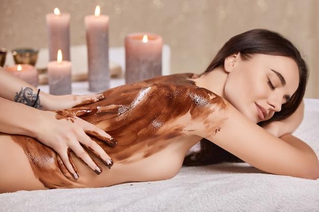 Mulher bonita recebe massagem com máscara de chocolate em salão de beleza por esteticista com velas