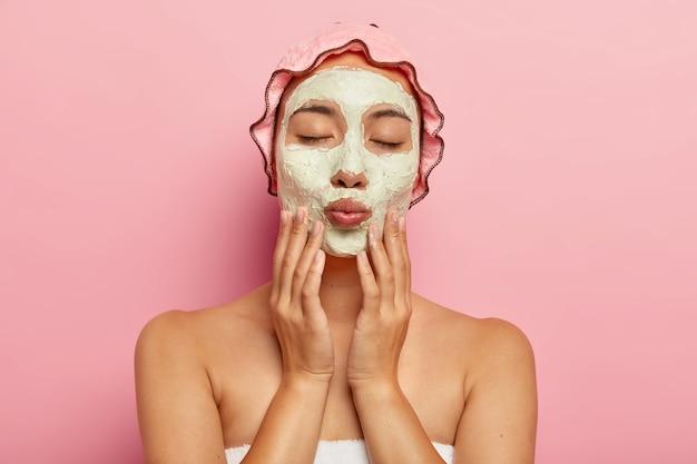 Mulher bonita recebe tratamentos de beleza, mantém os olhos fechados, lábios dobrados, tem expressão calma e gentil, aplica máscara facial de argila, fica de pé contra a parede rosa. procedimento anti-envelhecimento