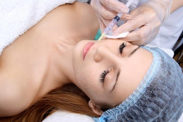 Mulher bonita recebe uma injeção nos lábios.