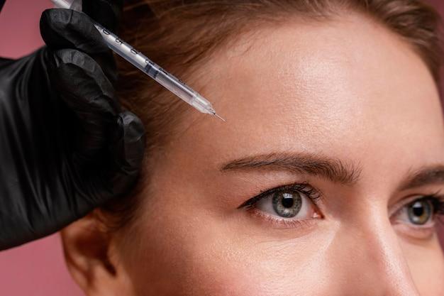 Mulher bonita recebendo injeção no rosto