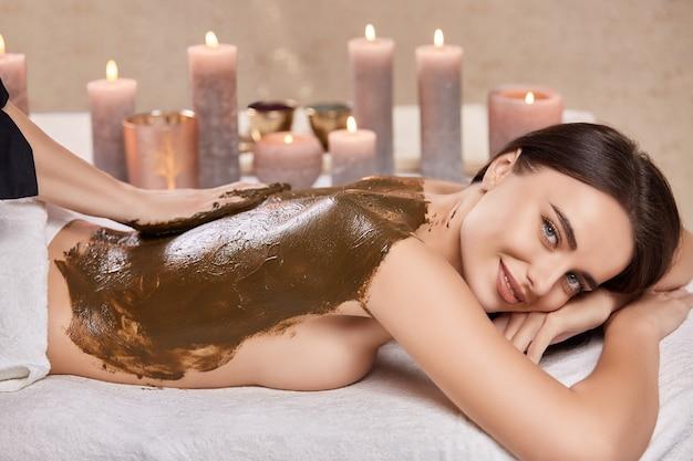 Mulher bonita recebendo massagem de colocato no spa e