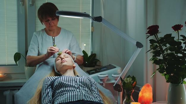 Mulher bonita, recebendo massagem facial com rolo de jade no salão de beleza com pouca luz ao redor