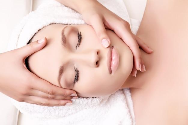 Mulher bonita, recebendo massagem facial e tratamento de spa