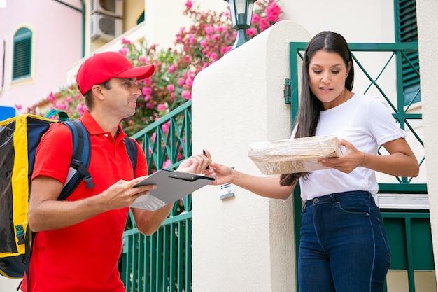 Mulher bonita recebendo pacote do entregador de uniforme vermelho. correio caucasiano feliz carregando mochila térmica amarela, sorrindo e entregando o pedido ao cliente. serviço de entrega e pós-conceito