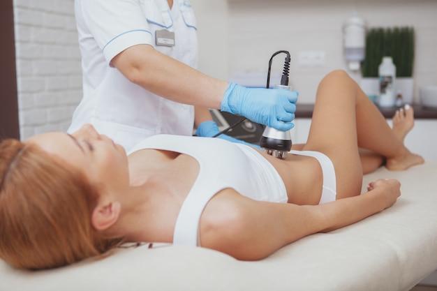 Mulher bonita, recebendo tratamento de levantamento de rf por cosmetologista