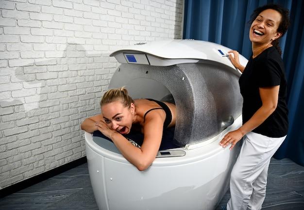 Mulher bonita, recebendo um banho de temperatura fria na cápsula de spa. conceito de cuidados com o corpo