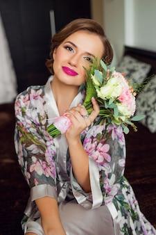 Mulher bonita recém-casada começa a preparação do dia do casamento com roupão floral
