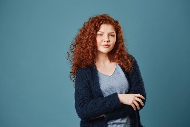Mulher bonita relaxada com cabelos ondulados ruivos e sardas de mãos cruzadas na frente dela, olhando com expressão confiante.