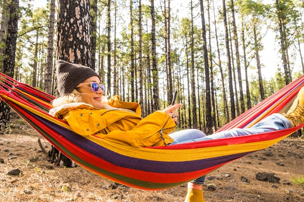 Mulher bonita relaxada curtindo rede e estilo de vida com a natureza ao redor - conceito de pessoas e ambiente com postura feminina e repouso e mensagem com conexão de roaming de telefone na floresta