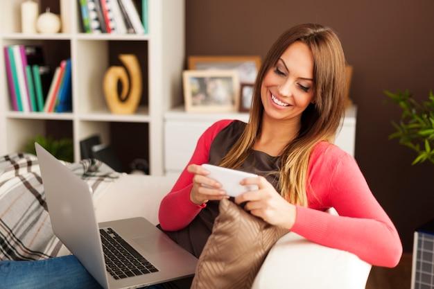 Mulher bonita relaxando com tecnologia moderna em casa