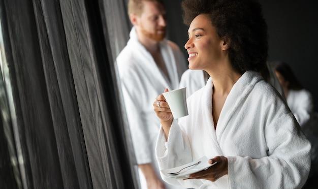 Mulher bonita relaxando em um spa de hotel de luxo vestindo roupão de banho, olhando para a janela e bebendo café
