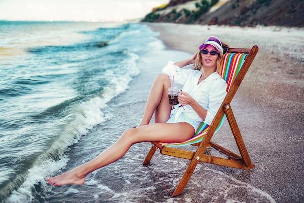 Mulher bonita relaxando em uma espreguiçadeira na praia e bebendo água com gás