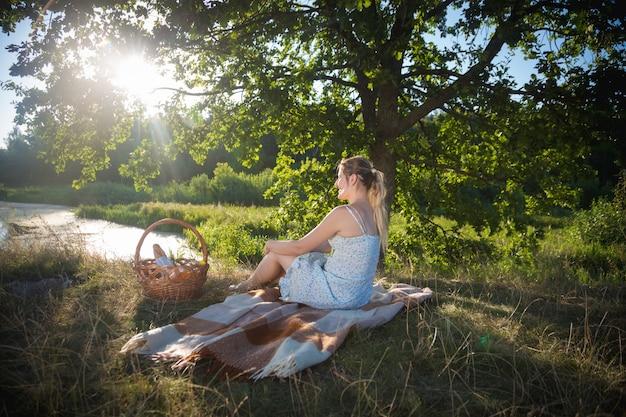 Mulher bonita relaxando no cobertor debaixo da árvore e olhando o pôr do sol