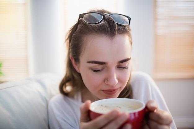 Mulher bonita relaxando no sofá com café na sala de estar
