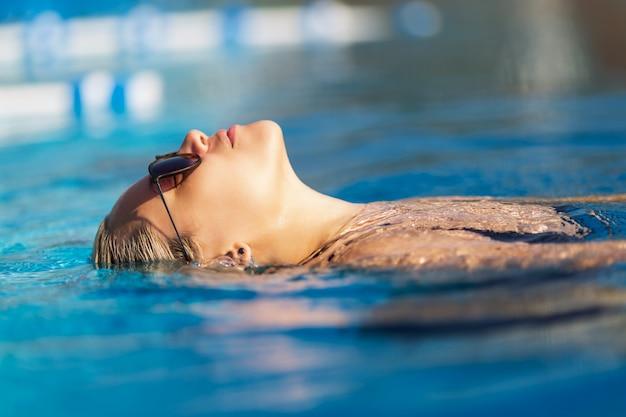Mulher bonita relaxante à beira da piscina de luxo