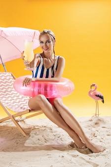 Mulher bonita relaxante com coquetel fresco frio após nadar alegre